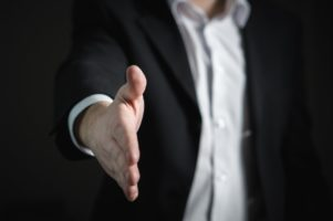 man in suit reaching out hand for handshake